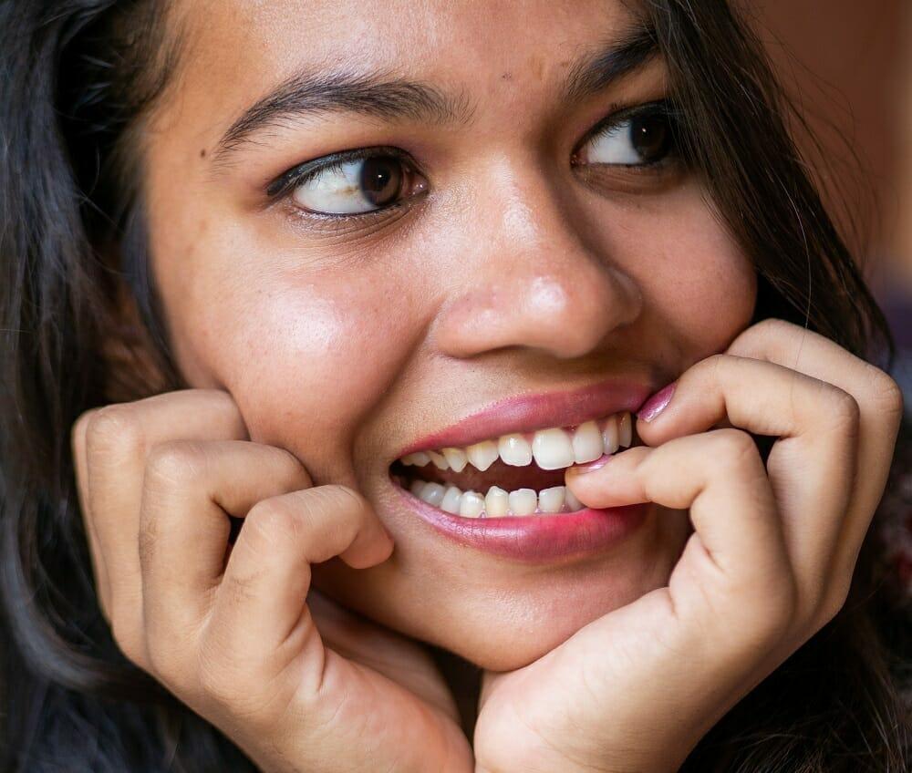 Moça jovem sorrindo ao roer unha