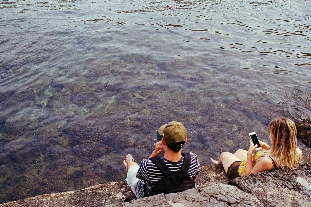 Casal de adolescentes usando o celular em um lago
