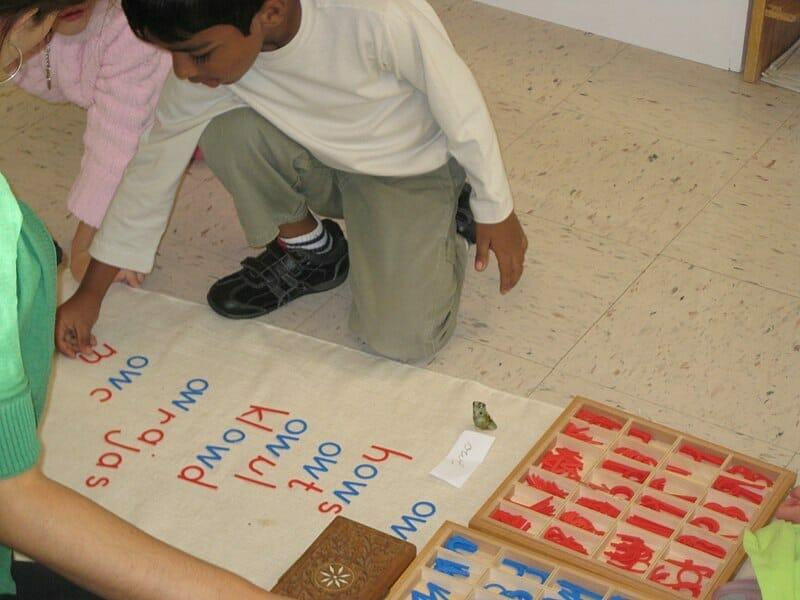 Alunos brincando com um alfabeto móvel em escola montessoriana