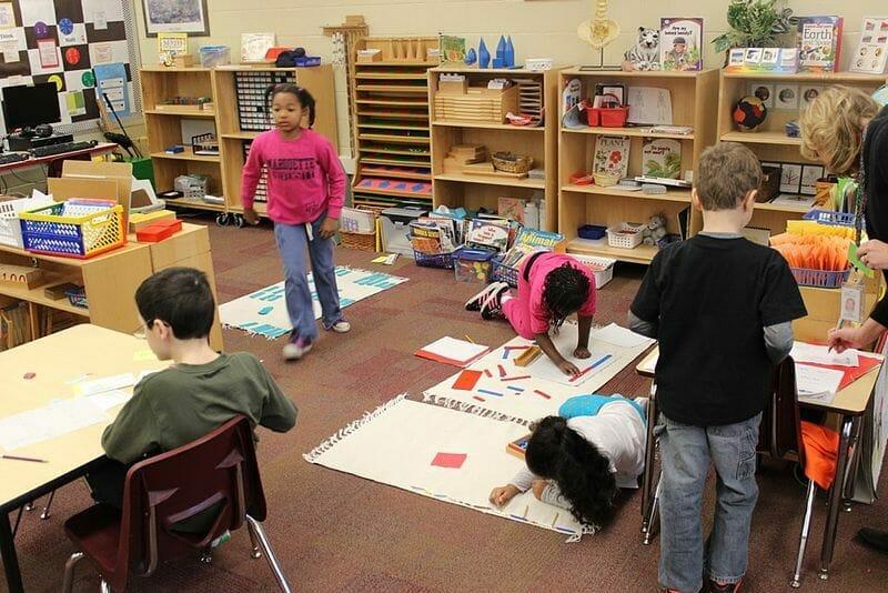 Alunos estudando em uma sala de aula de escola montessoriana