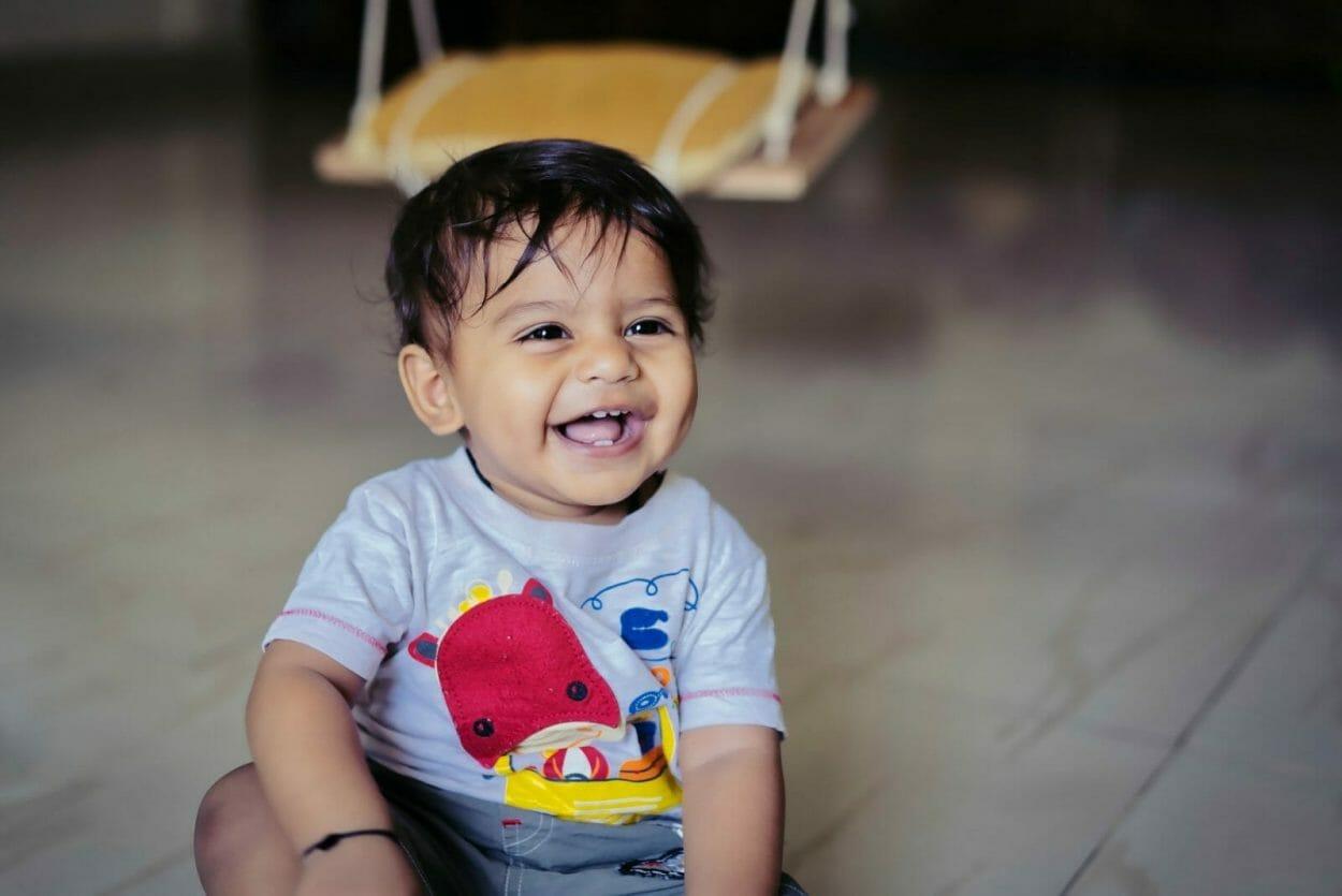 Bebê indiano sentado no chão e sorrindo