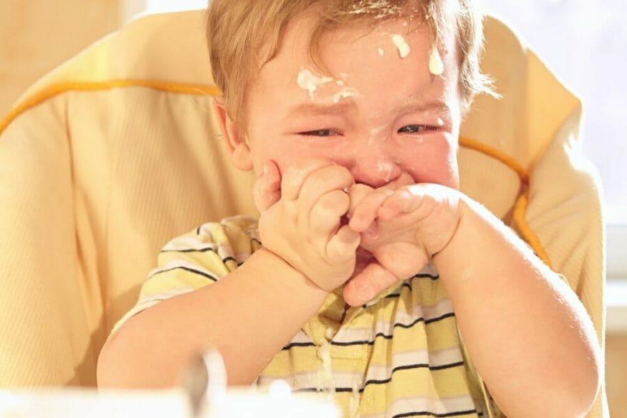 Bebê chorando sentado na cadeirinha, sujo de comida
