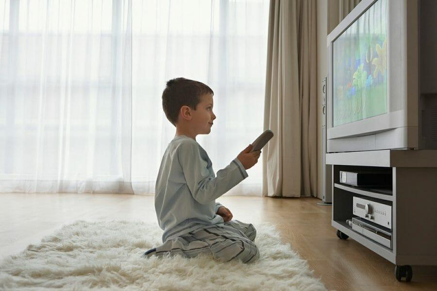 Criança ajoelhada assistindo TV