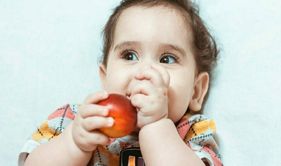 Criança brincando com fruta na boca