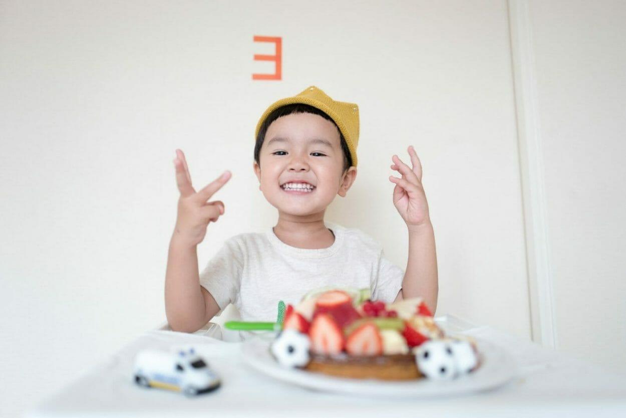 criança oriental sorrindo sentada em uma mesa com um carrinho e um bolo de aniversário