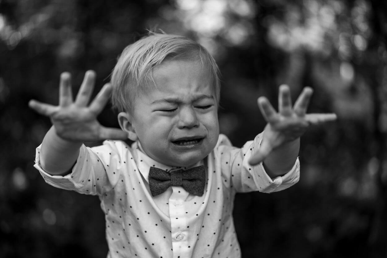 Foto preta e branca de criança com roupa social chorando, com as mãos para a frente