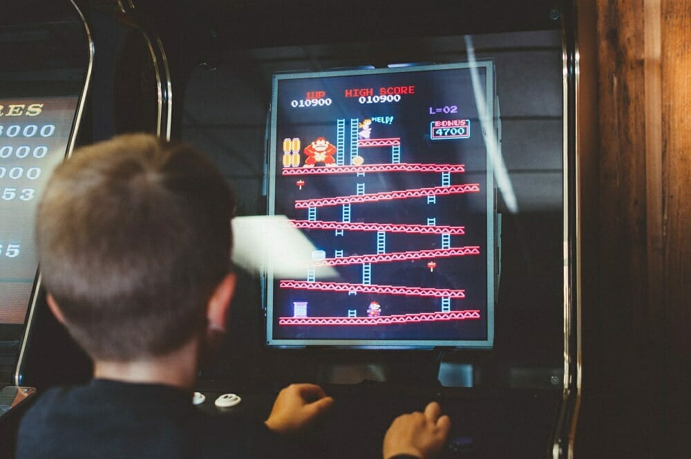 Criança jogando Champ Kong em um videogame antigo
