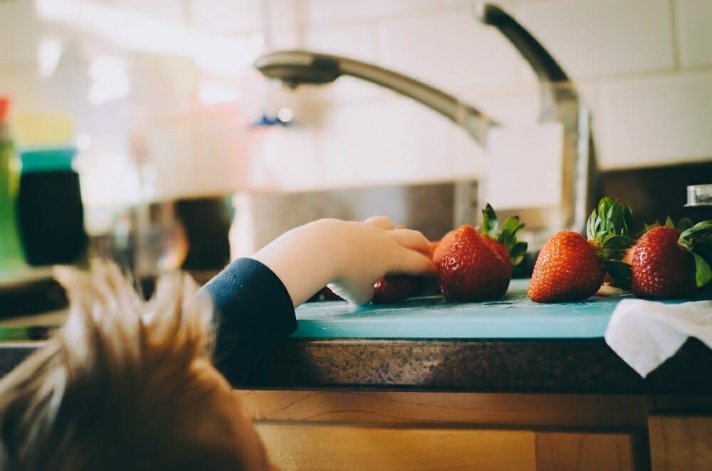 Criança pegando morango que está em cima de um balcão