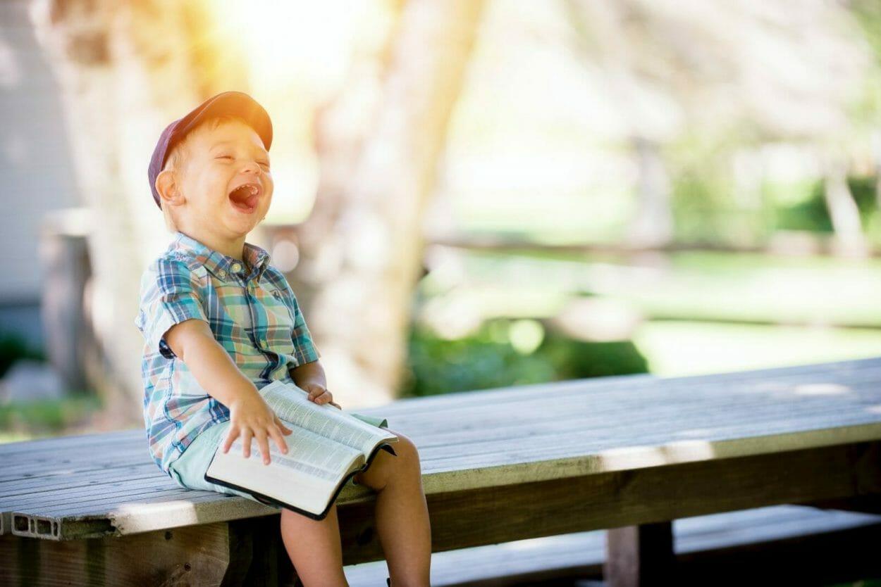 criança sorrindo em um banco ao ar livre com um livro no colo