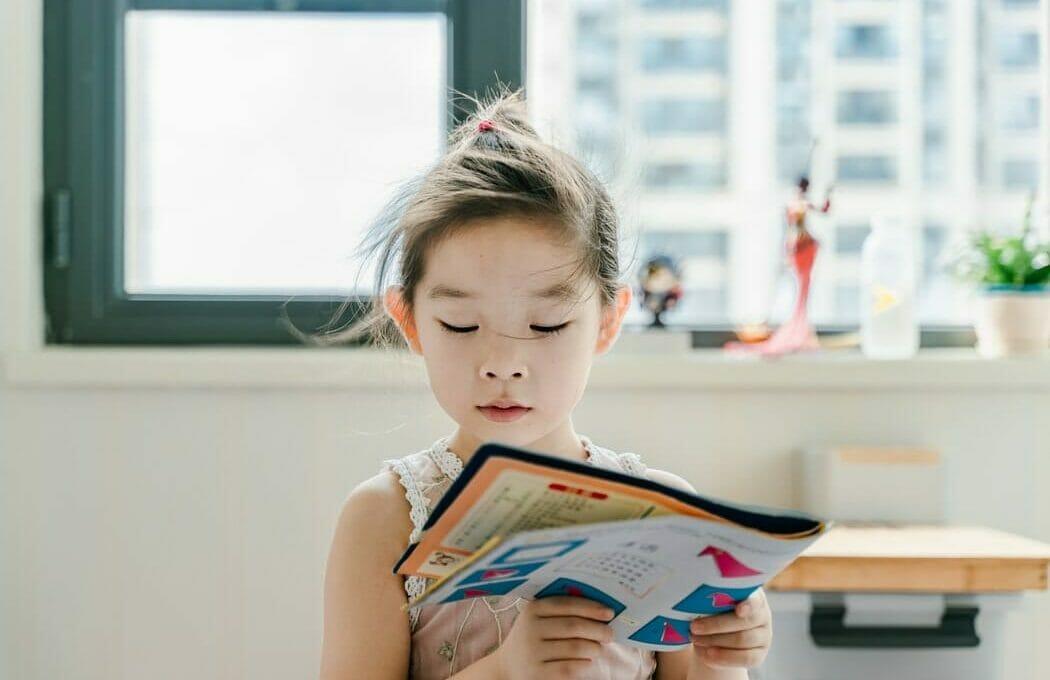 Criança lendo livro colorido
