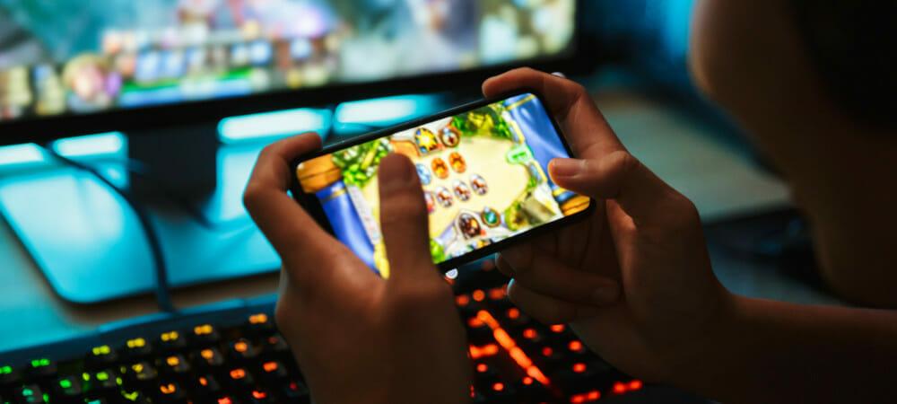Criança se divertindo jogando no celular, com computador gamer ligado no fundo