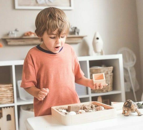 Criança se surpreendendo com caixa de brinquedos educativos