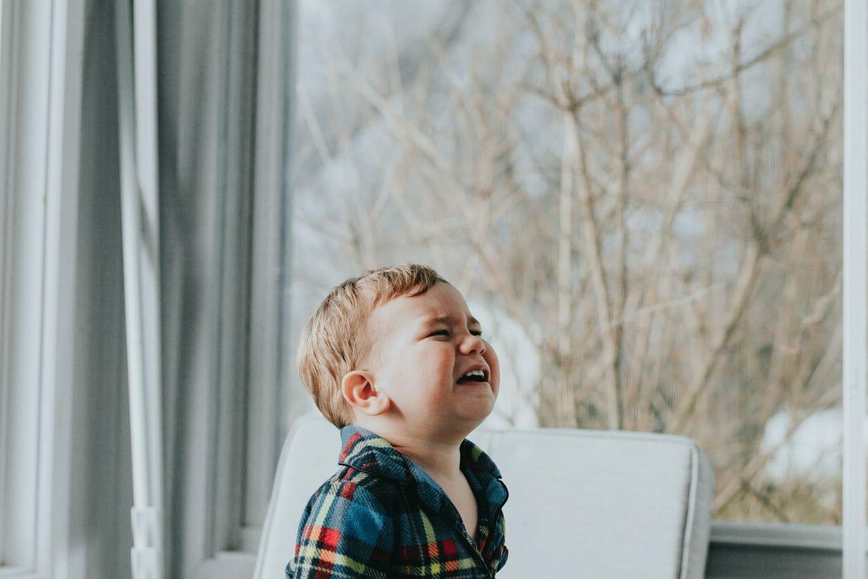 Criança sentada em poltrona chorando