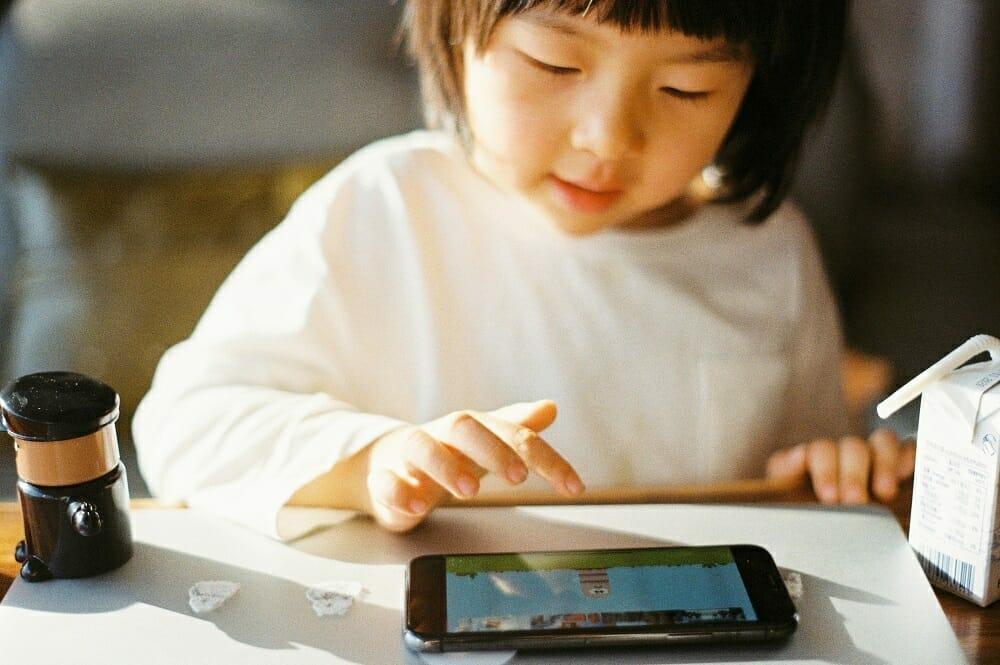 tempo de tela na infância: criança usando celular para jogar