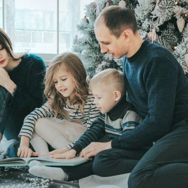 Pais e duas crianças pequenas sentados no chão e lendo juntos
