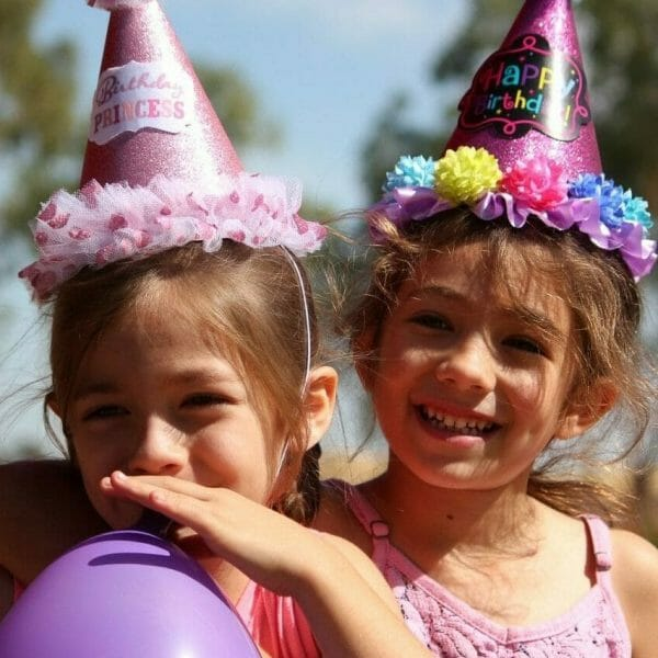 Duas meninas comemorando o aniversário. Ambas estão com chapéus de festa coloridos e uma assopra um balão roxo