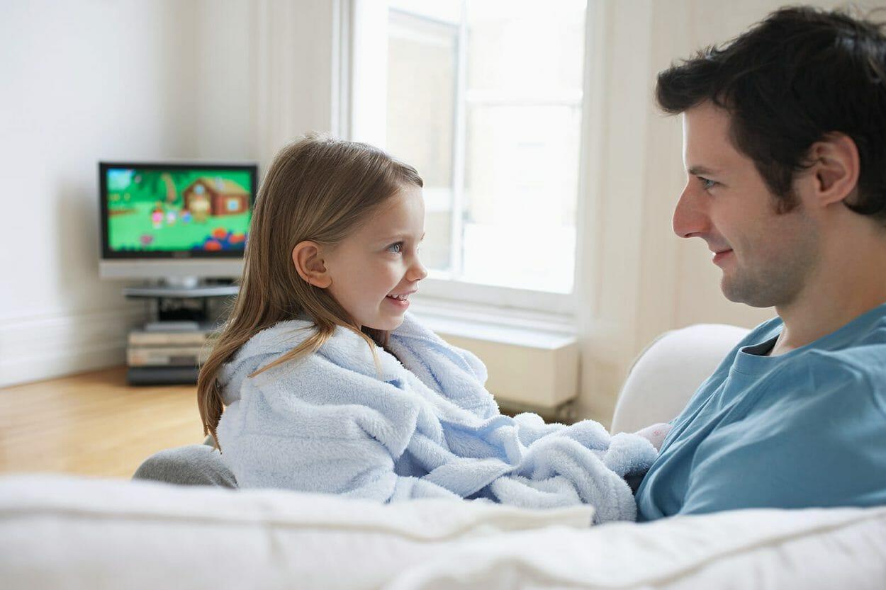 filha e pai brincando frente tv