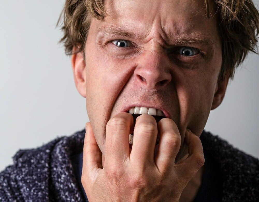 homem nervoso com a mão na boca roendo unhas