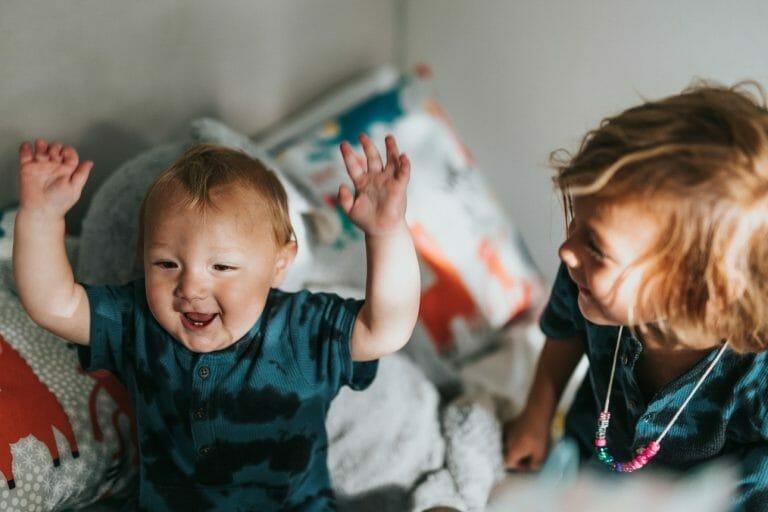 Irmão e irmã brincando na cama
