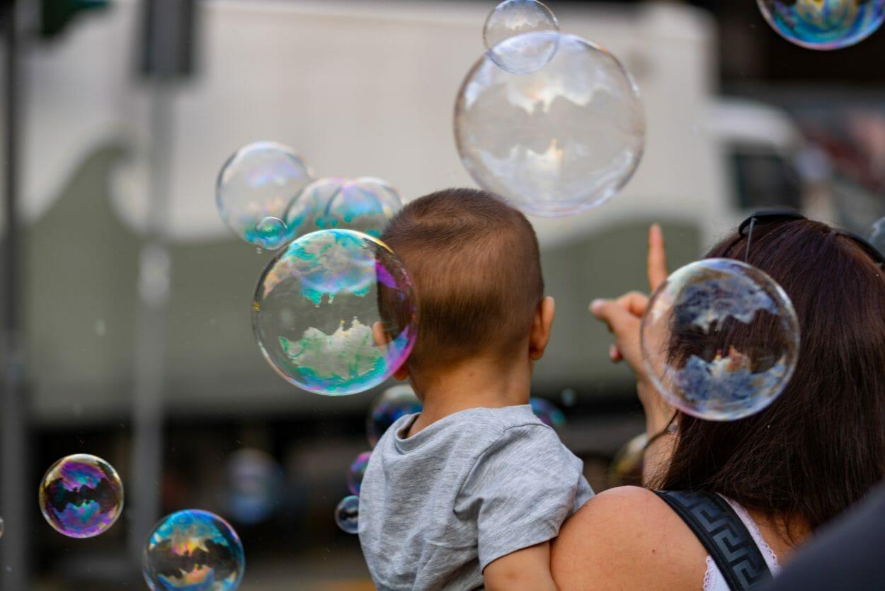 Mãe segurando bebê no colo fora de casa e apontando para bolhas de sabão no ar