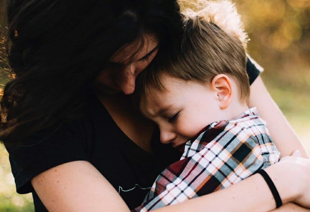 Filho chorando no colo da mãe, que abraça a criança para consolar