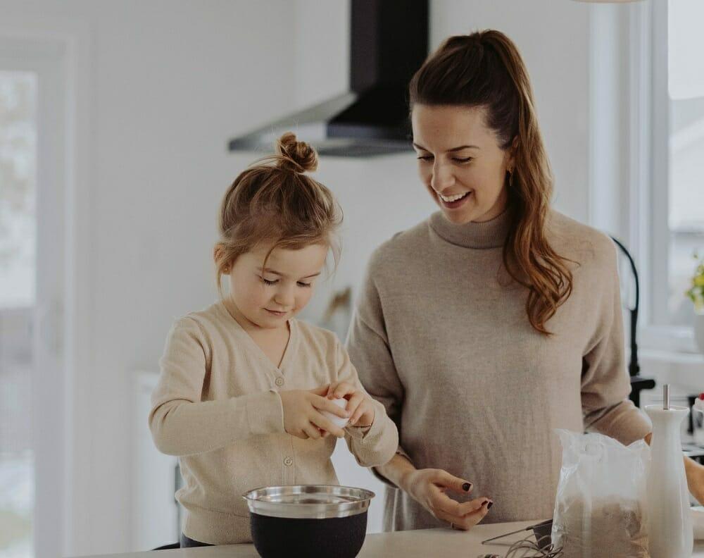 Mãe e filha fazendo bolo juntas. Mãe observa enquanto criança quebra um ovo