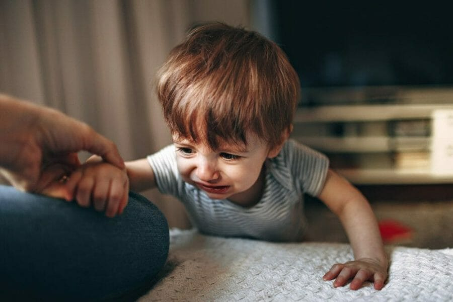 Criança chorando no chão depois de cair, tentando se levantar. Ele apoia um dos braços na mãe
