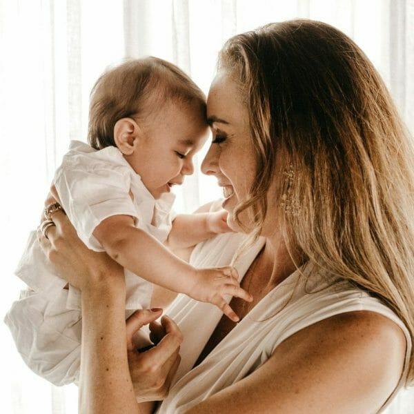 mãe sorrindo e segurando filho bebê no colo