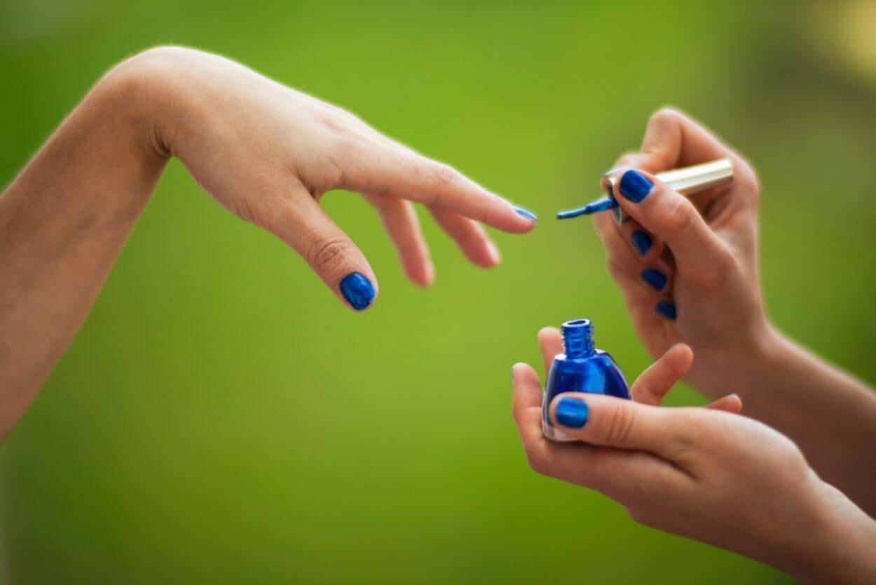 Manicure pintando as unhas da mão
