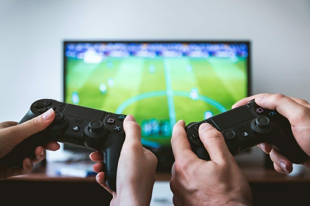 Mãos segurando controles e jogando game de futebol