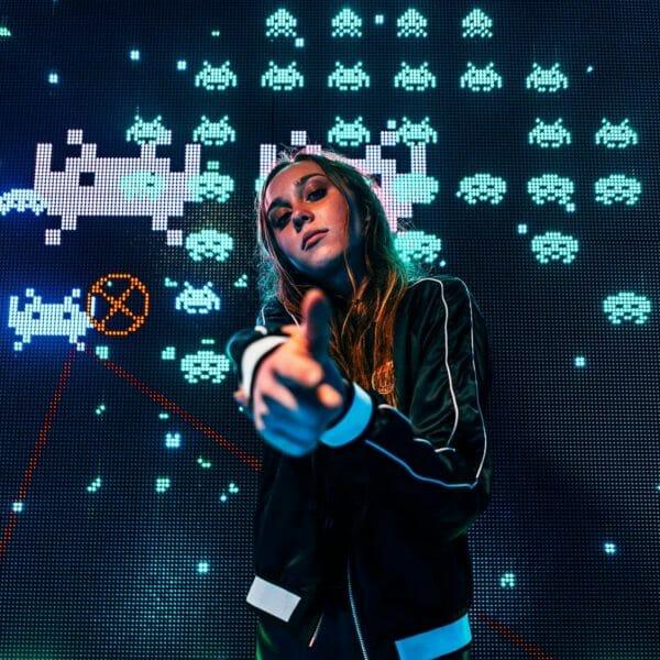 Mulher gamer na frente do jogo Space Invaders