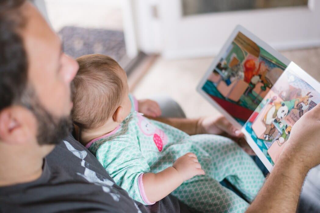 Pai com filho bebê sentado no colo lendo um livro infantil