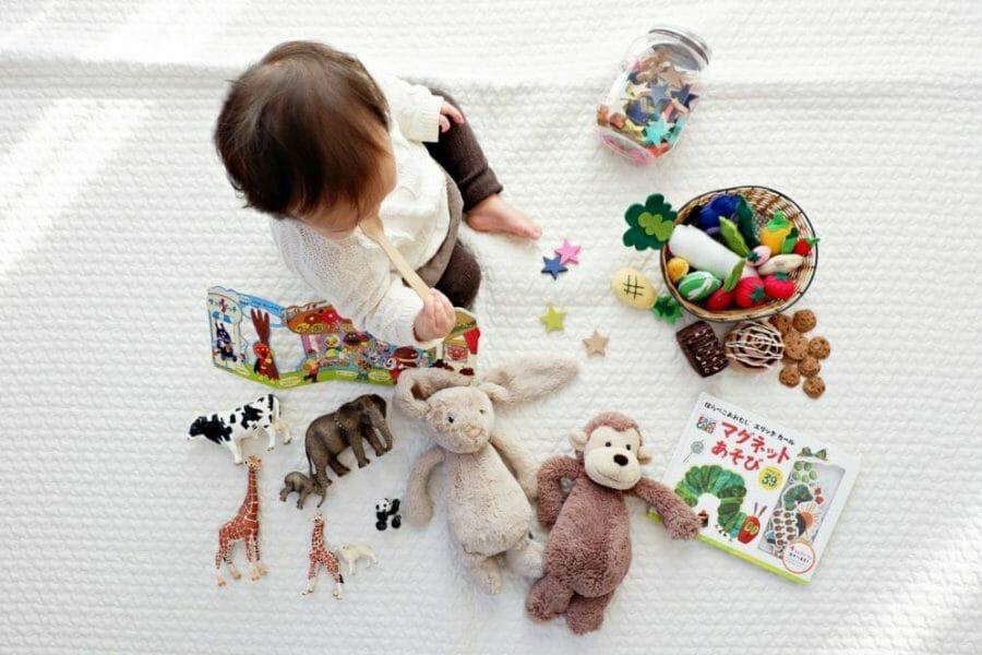 Bebê sentado no chão com diversos brinquedos espalhados ao redor