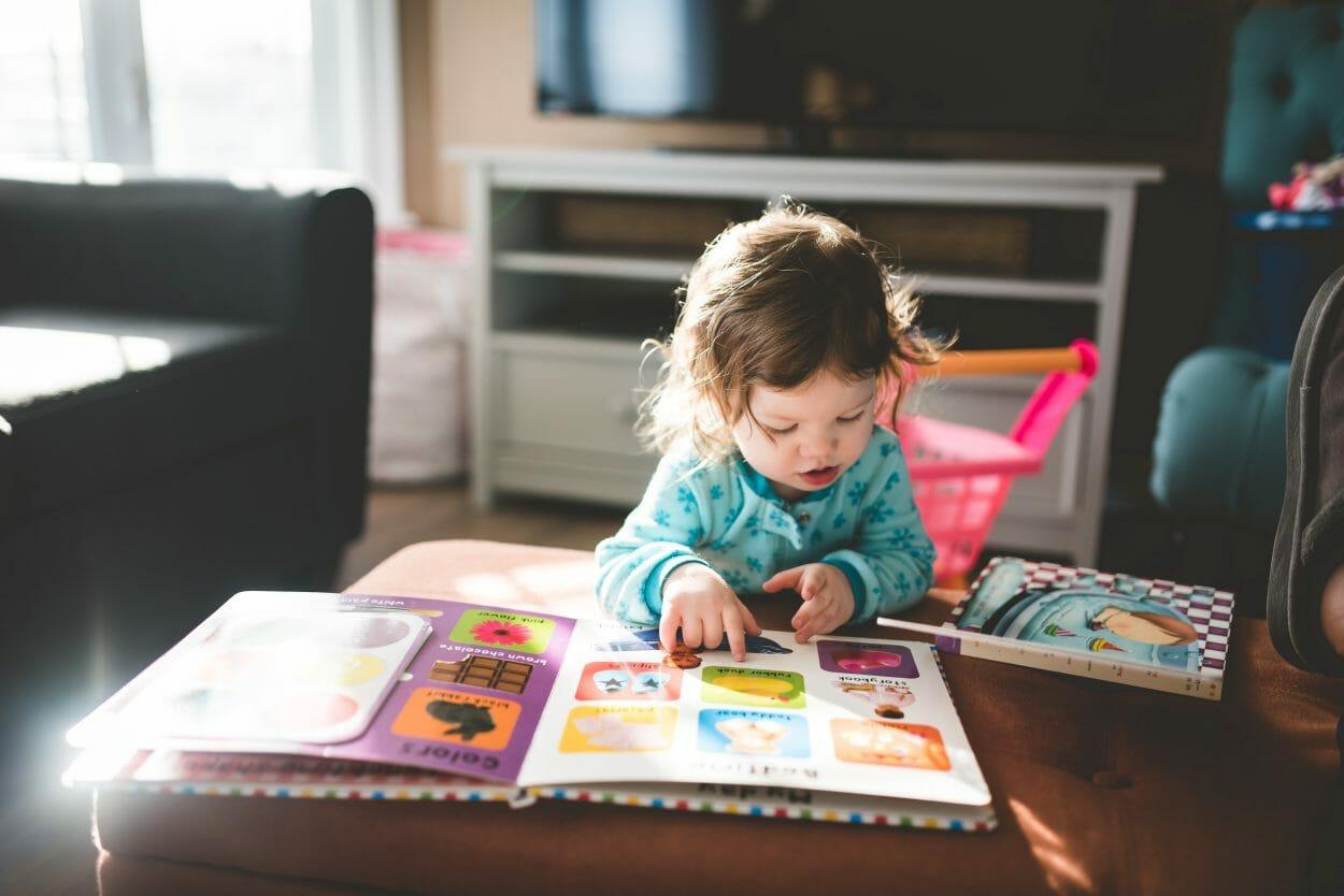 Criança pequena passando os dedos por cima de um livro colorido na sala de estar.